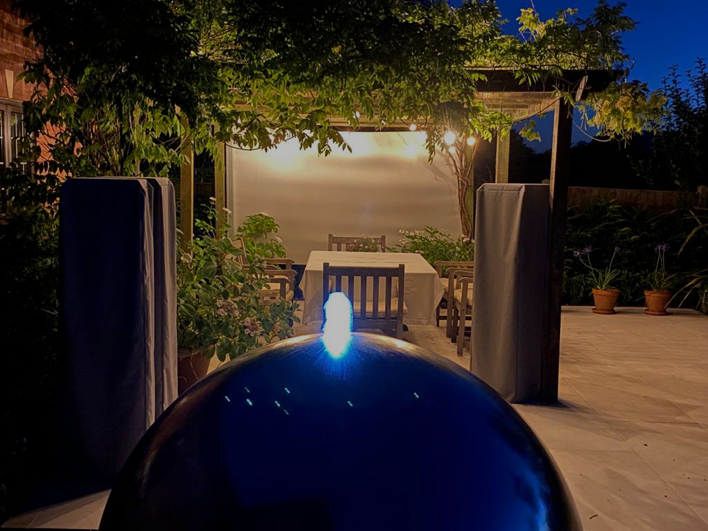 A dark corner with a pergola was opened up and lighting now makes it a cosy and inviting space